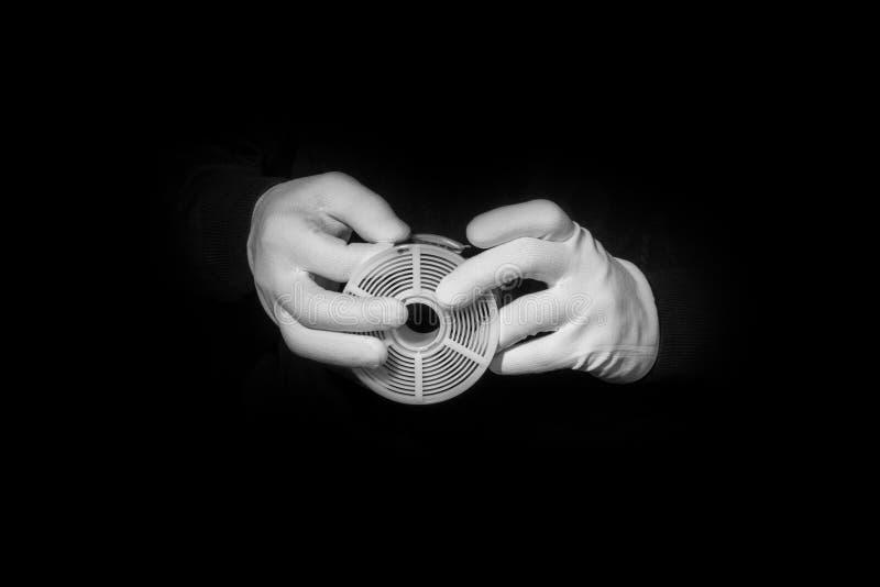 Il laboratorio, mani in guanti bianchi tiene il nero e un film, camera oscura, developmen fotografia stock libera da diritti