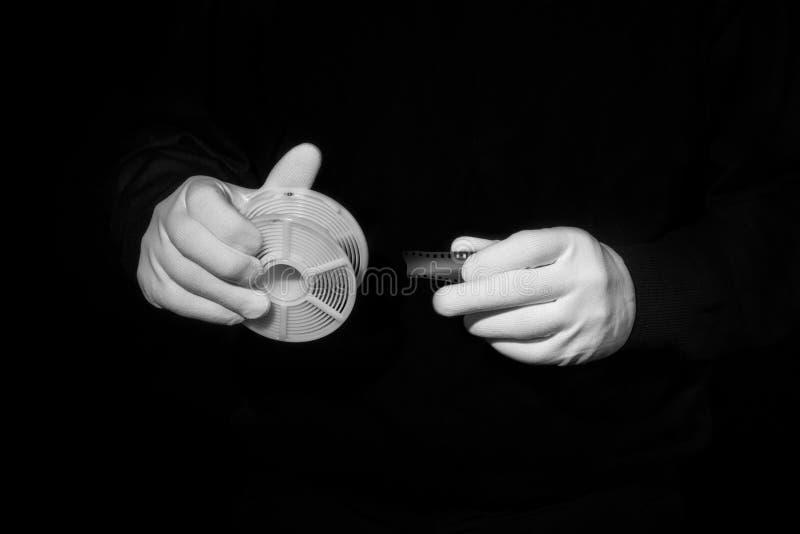 Il laboratorio, mani in guanti bianchi tiene il nero e un film, camera oscura, developmen immagine stock