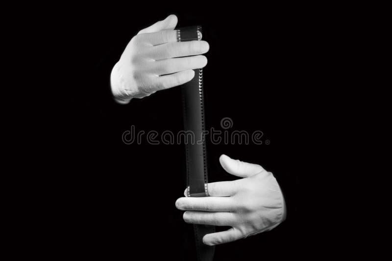 Il laboratorio, mani in guanti bianchi tiene un film in bianco e nero fotografia stock libera da diritti