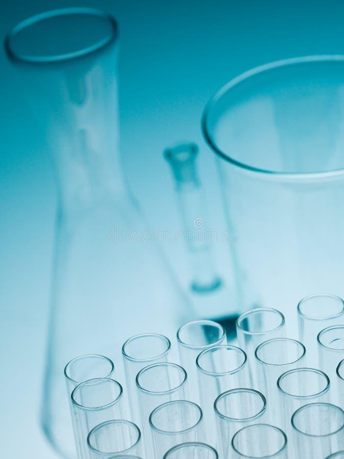 Il laboratorio sperimenta cristalleria sul fondo blu di pendenza fotografia stock libera da diritti