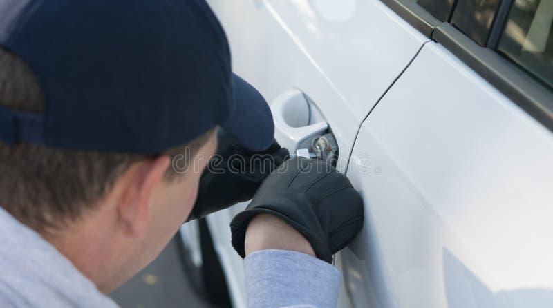 Il ladro del guanto infrange la legge, incisioni fissa l'automobile per ottenere dentro immagine stock libera da diritti