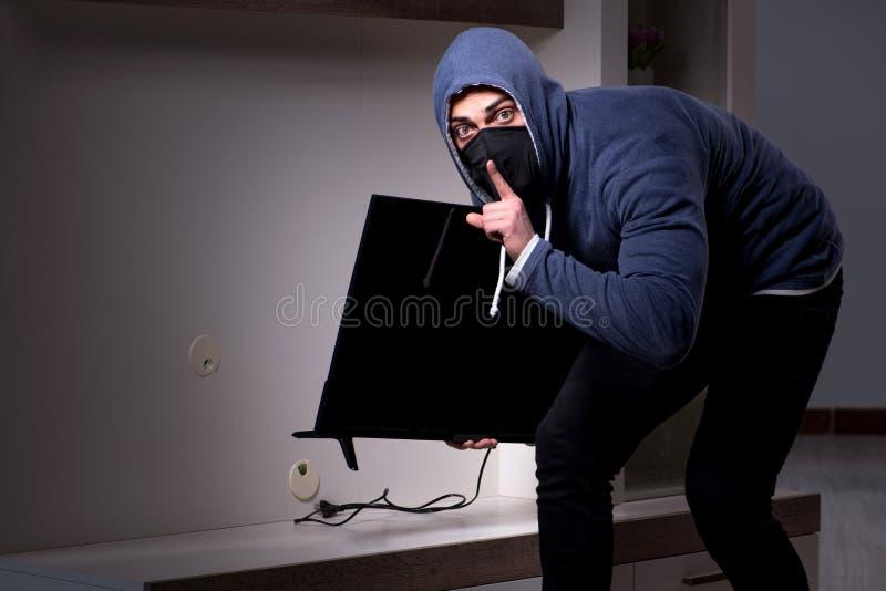 Il ladro dello scassinatore che ruba TV dal condominio immagini stock libere da diritti
