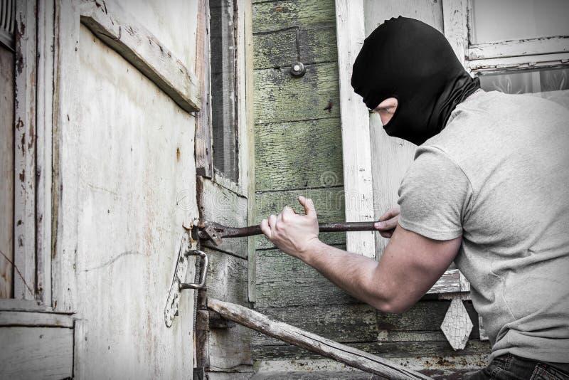 Il ladro mascherato rompe la porta di serratura nella Camera fotografie stock