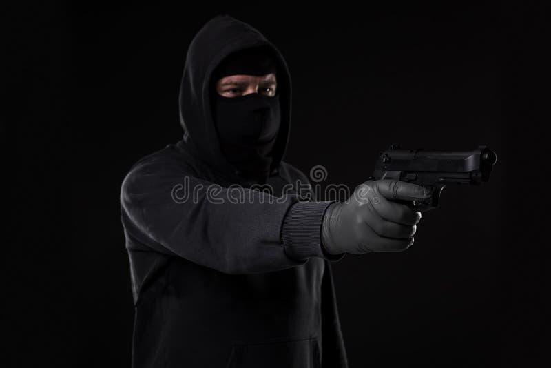 Il ladro in una maschera con una pistola ha indicato il lato su un fondo nero immagini stock libere da diritti