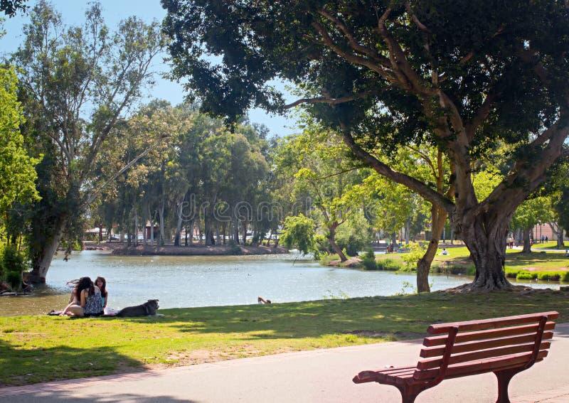 Il lago, banco, ragazze con il cane e si rilassa nel parco di Yarkon, Tel Aviv, Israele fotografia stock libera da diritti