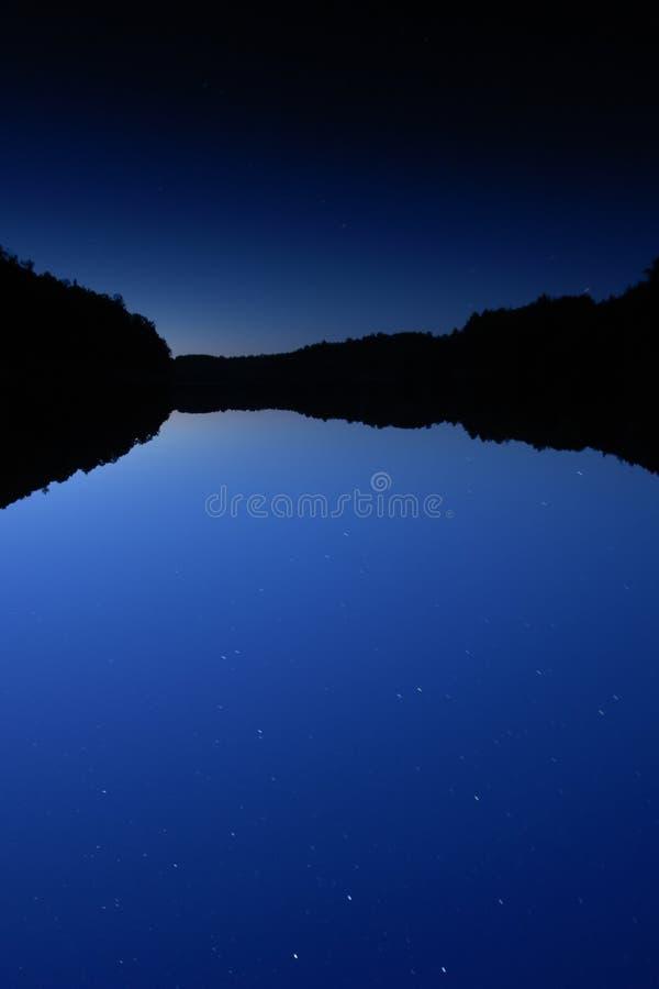 Il lago blu profondo alla notte con l'orientamento Stars fotografia stock