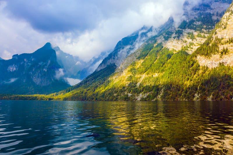 Il lago ? circondato dalle alte montagne immagine stock libera da diritti