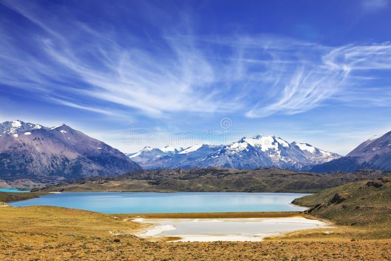 Il lago circondato dalle montagne innevate immagine stock