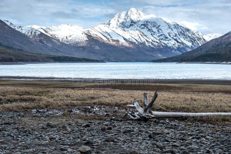Il lago d'Alasca turquoise con neve ha ricoperto le montagne come contesto fotografia stock
