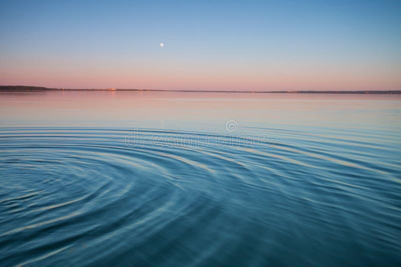 Il lago del turchese all'alba piccole onde simmetriche fotografia stock libera da diritti