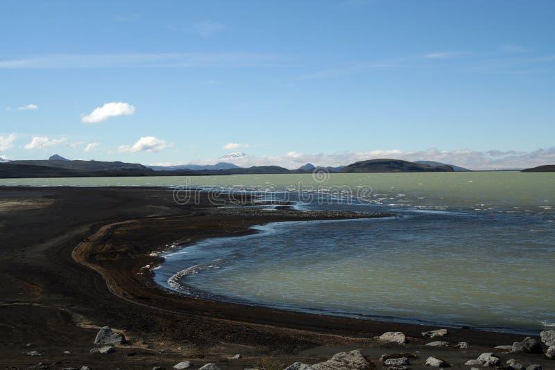 Il lago Hálslón con la spiaggia e la neve vulcaniche nere ha ricoperto le montagne in Islanda fotografia stock libera da diritti