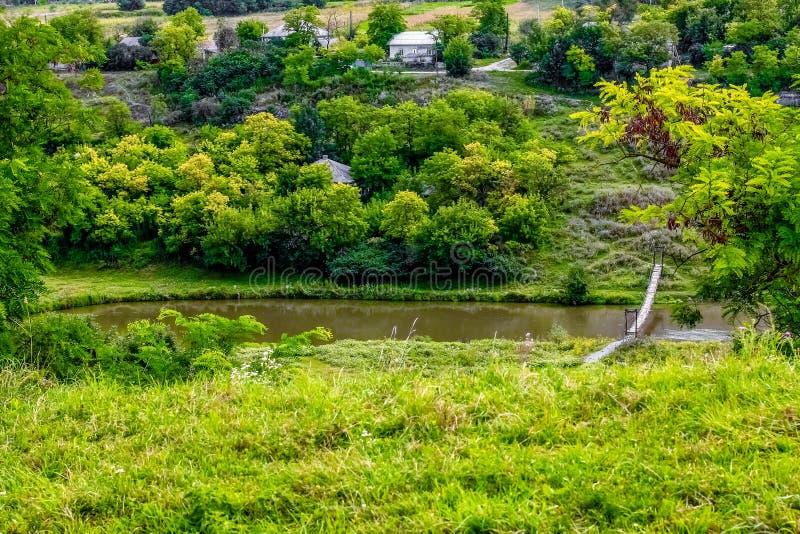 Il lago verde vicino alle case ed agli alberi fotografia stock