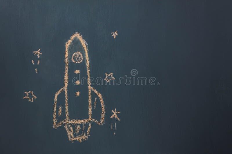 Il lancio fatto a mano della nave del razzo del disegno di disposizione piana/decolla allo spazio con la stella sulla lavagna dal fotografia stock libera da diritti