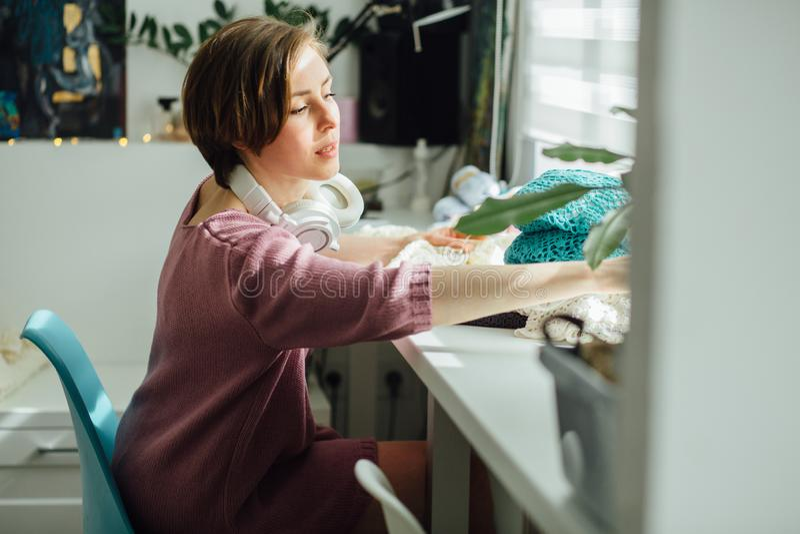 Il lato del progettista della donna che tricotta il vestito tenero con lavora all'uncinetto al lavoro creativo delle free lance f immagini stock