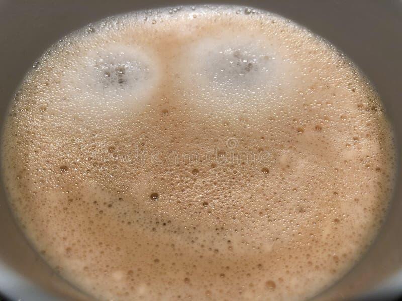 Il latte del cappuccino del caffè di mattina con il fronte felice benvenuto sorridente del cioccolato o della schiuma ha un giorn immagini stock