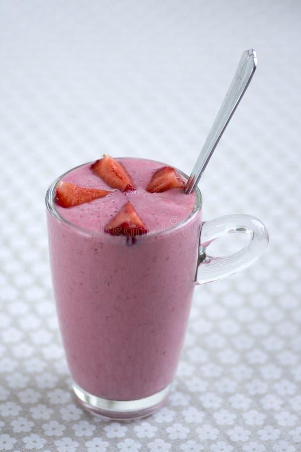 Il latte e le fragole freschi bevono nel vetro sul frappé saporito e sano floreale della tovaglia del modello, della frutta immagine stock libera da diritti