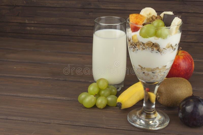 Il latte fresco nel vetro ed i muesli fanno colazione su una tavola di legno Farina d'avena con latte e cagliata, pasti per gli a fotografia stock libera da diritti