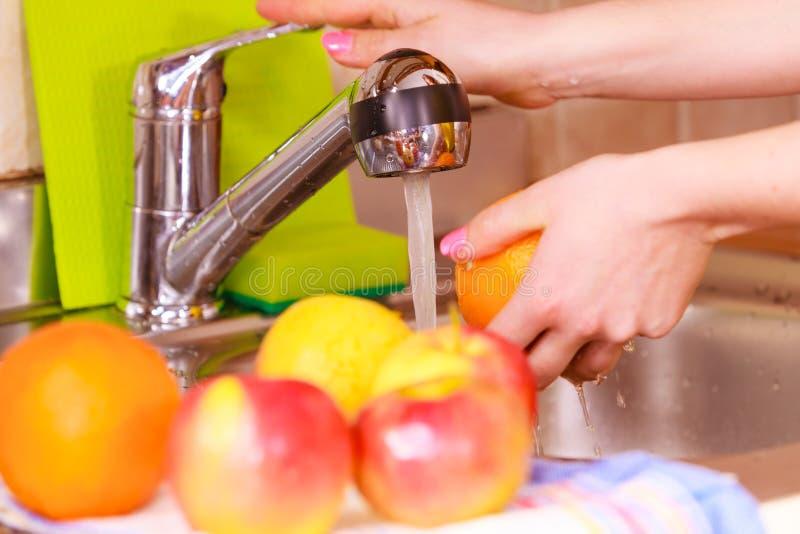 Il lavaggio della casalinga fruttifica in cucina sotto la corrente dell'acqua immagine stock