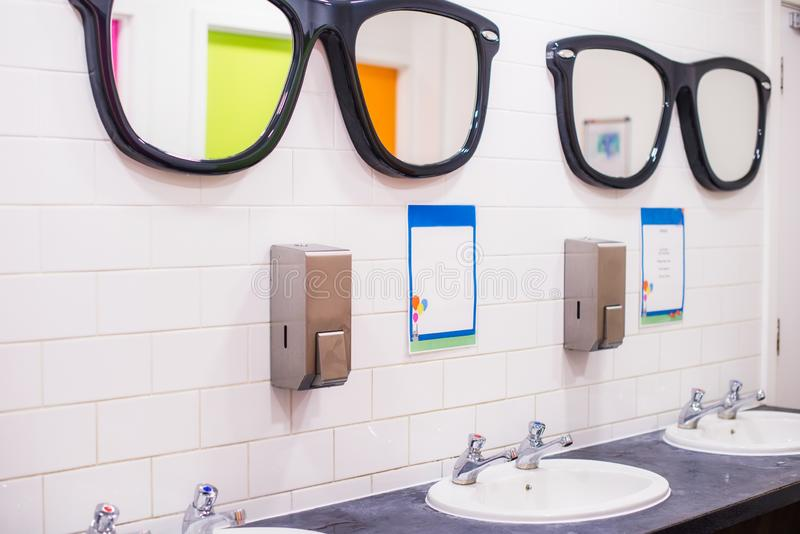 Il lavandino del lavaggio ed i grandi specchi sotto forma dei vetri nella toilette pubblica, fila delle due gru inglesi il lavabo fotografia stock libera da diritti