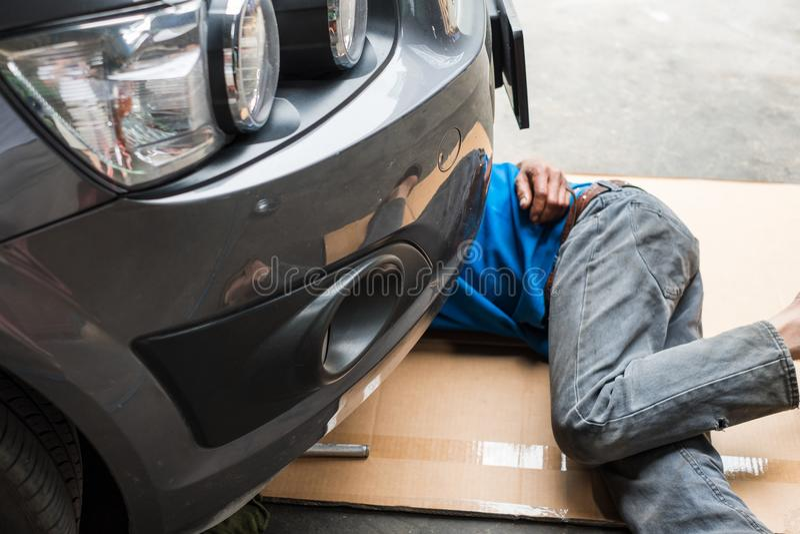 Il lavoratore è sotto l'automobile per cambiare l'olio per motori immagini stock libere da diritti