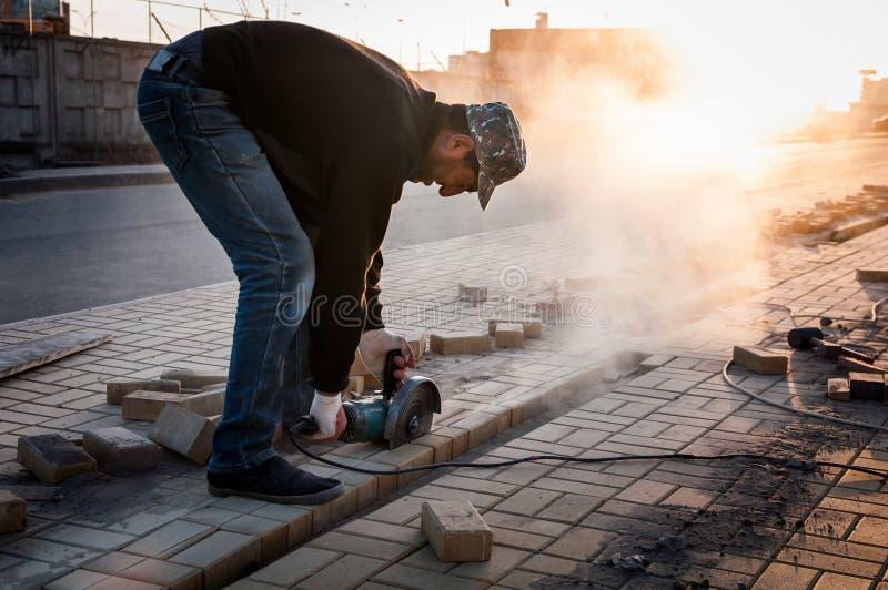 Il lavoratore al cantiere sega i materiali da costruzione fotografia stock libera da diritti