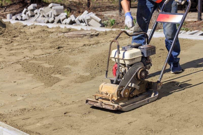 Il lavoratore avvia un compattatore della benzina per la piantatura del suolo sabbioso per la stenditura delle lastre per pavimen immagine stock libera da diritti