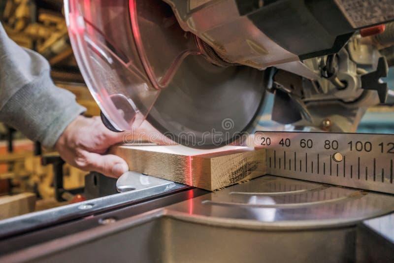 Il lavoratore caucasico del carpentiere dell'uomo che lavora guidando la circolare ha visto per tagliare i bordi fotografia stock