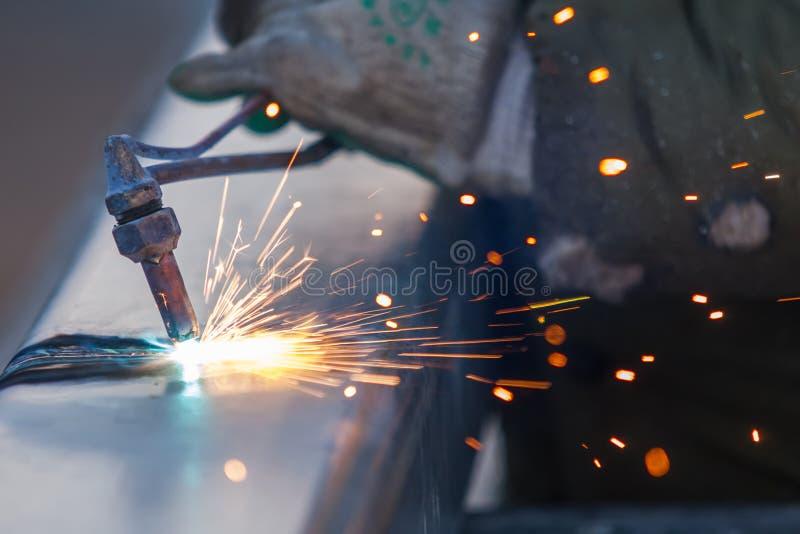 Il lavoratore che taglia il tubo d'acciaio facendo uso della torcia del metallo ed installa il bordo della strada immagini stock