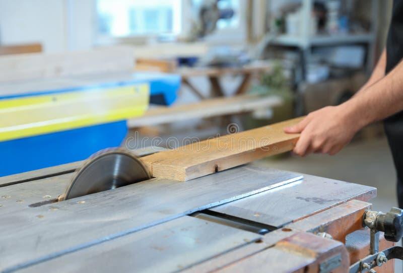 Il lavoratore che usando la circolare ha visto al negozio di carpenteria fotografia stock libera da diritti