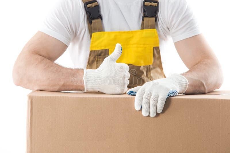 Il lavoratore con il pollice su che sta dietro le scatole con gli oggetti ha isolato la o immagine stock