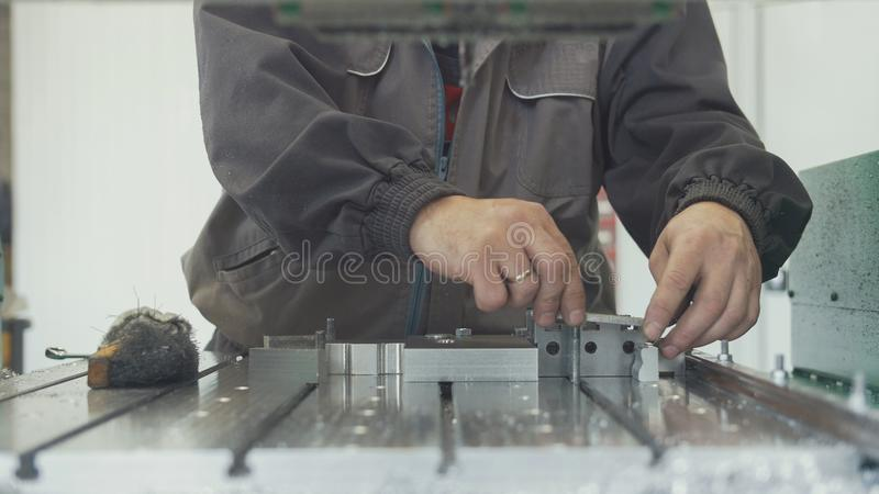 Il lavoratore con un'eliminazione di smussatura della ruspa spianatrice sbava sull'oggetto del metallo per la fabbricazione delle immagine stock