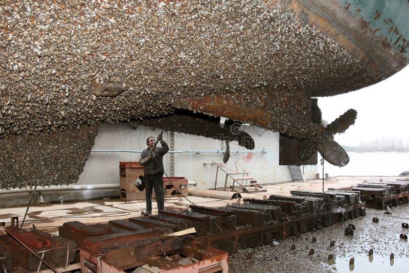 Il lavoratore del cantiere navale pulisce l'acqua di stuya della nave immagini stock libere da diritti