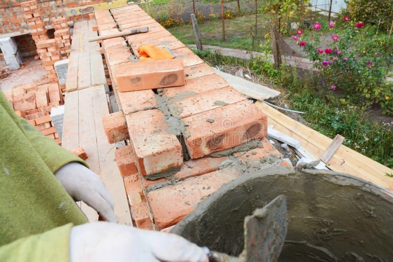 Il lavoratore del muratore che installa i blocchi rossi e che calafata la muratura del mattone congiunge la parete esteriore dell fotografie stock