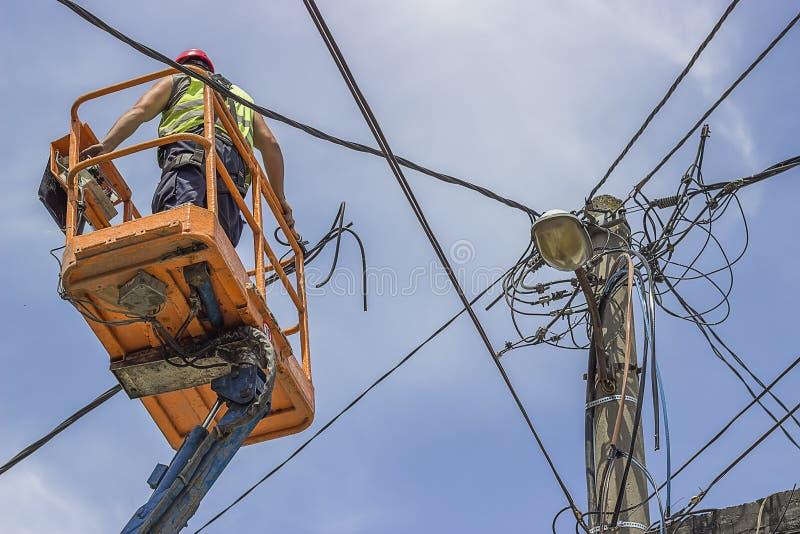 Il lavoratore del palo pratico installa i nuovi cavi su un palo elettrico immagini stock