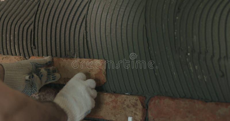 Il lavoratore del primo piano che applica il mattone taglia le mattonelle alla parete immagini stock libere da diritti