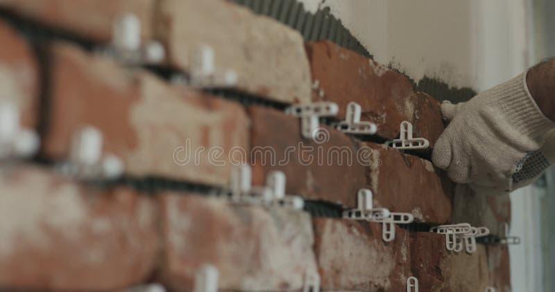 Il lavoratore del primo piano che applica il mattone taglia le mattonelle alla parete fotografie stock