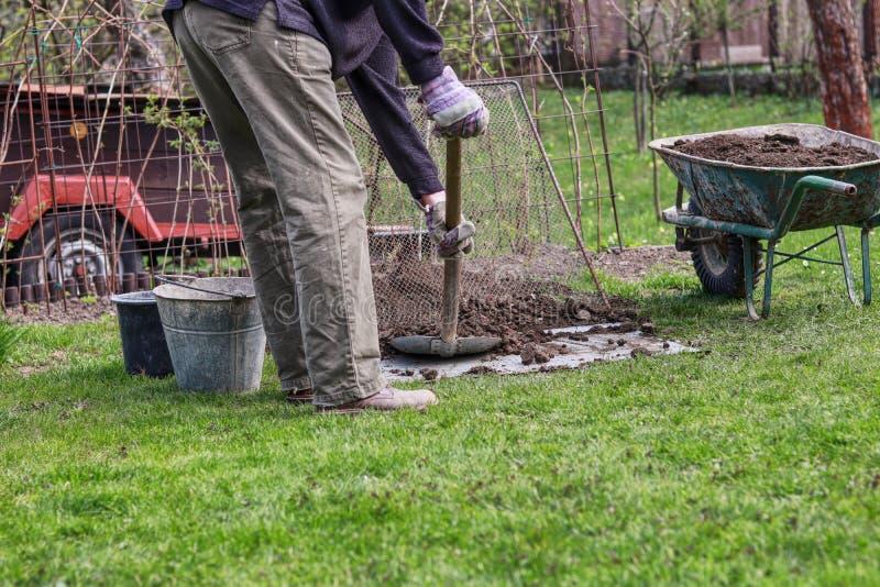 Il lavoratore dell'estate sta vagliando il suolo al il setaccio fatto a mano Lavoro di estate Abbellimento del giardino Carriola  fotografia stock libera da diritti