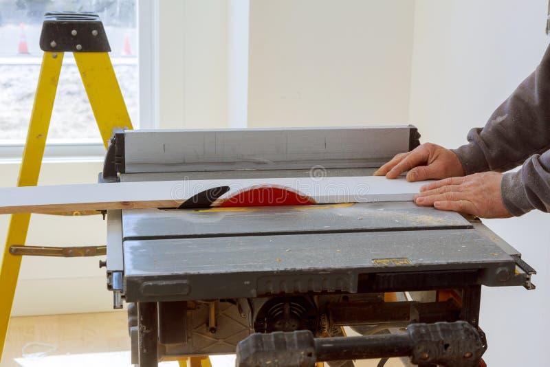 Il lavoratore dell'imprenditore edile facendo uso della circolare ha visto per tagliare i bordi su un nuovo progetto domestico di fotografia stock libera da diritti