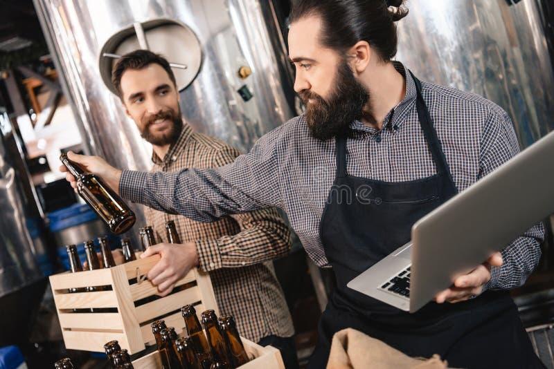 Il lavoratore della fabbrica di birra prende le bottiglie per la birra imbottigliante Produzione della birra del mestiere fotografia stock