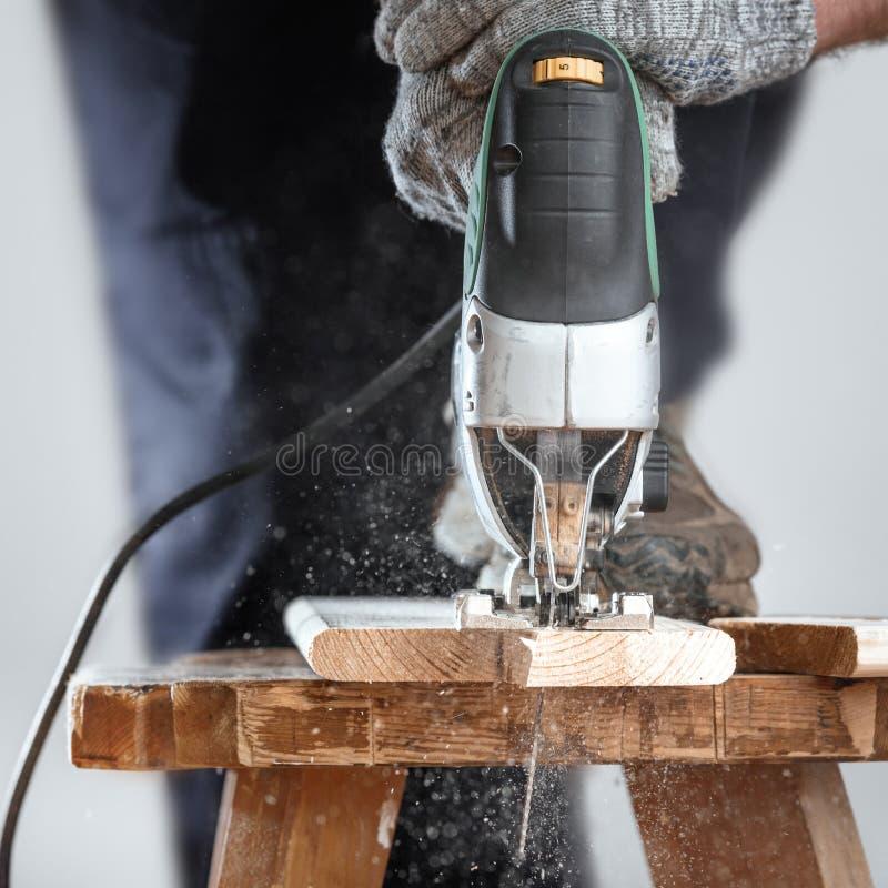 Il lavoratore di legno che taglia il pannello di legno con la maschera ha visto Taglio calcolato fotografie stock
