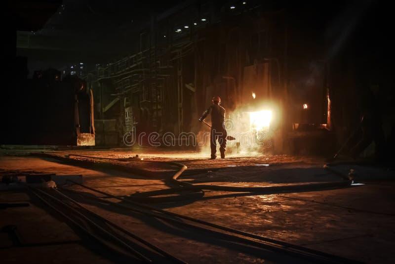 Il lavoratore di pianta getta il carbone nel forno di fusione Martin-Siemens immagine stock
