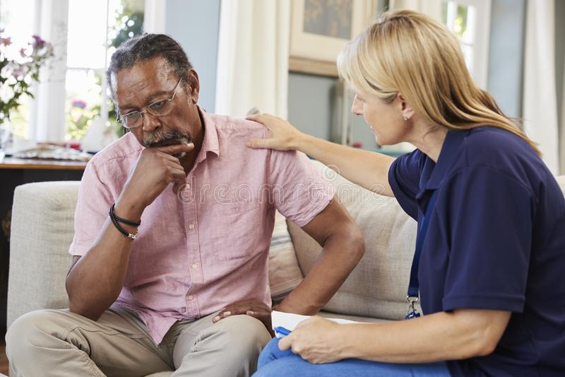 Il lavoratore di sostegno visita l'uomo senior che soffre con la depressione immagini stock