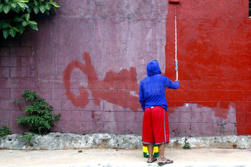 Il lavoratore dipinge una vecchia parete con pittura fresca fotografie stock libere da diritti