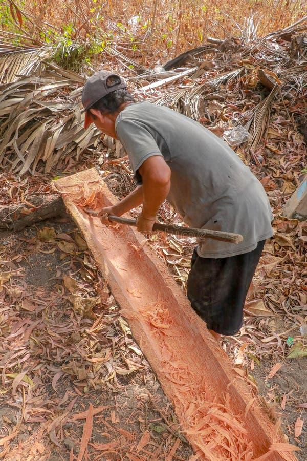 Il lavoratore elabora manualmente il tronco e le sgorbiature di albero con uno strumento semplice della depressione Grosso e lavo fotografia stock libera da diritti