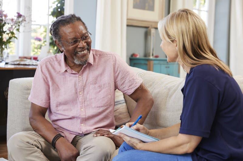 Il lavoratore femminile di sostegno visita l'uomo senior a casa immagini stock libere da diritti