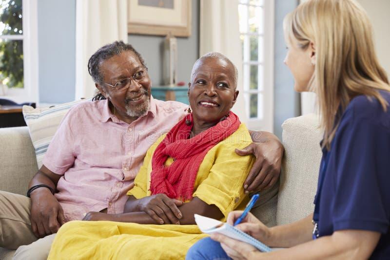 Il lavoratore femminile di sostegno visita le coppie senior a casa fotografia stock