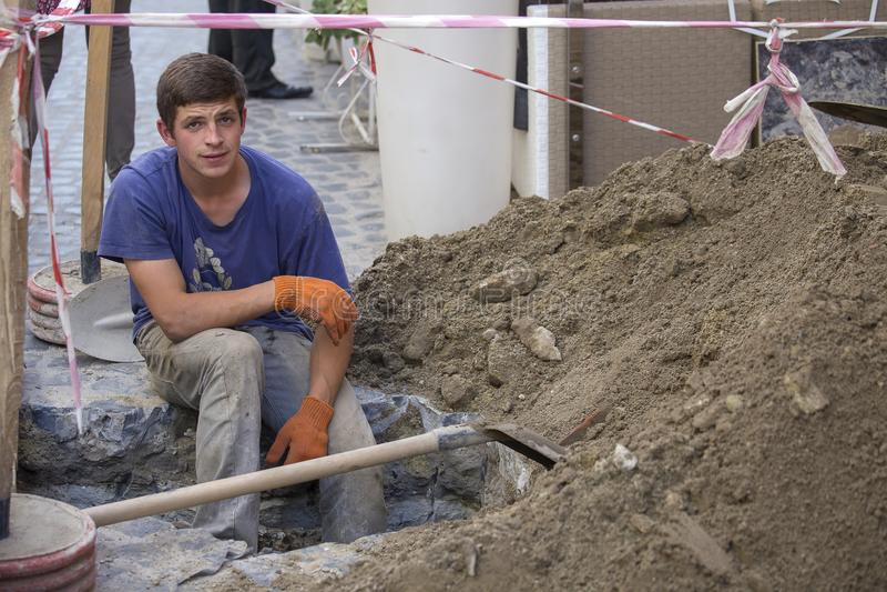 Il lavoratore ha scavato un pozzo per il lavoro della riparazione con una tubatura dell'acqua Tubi per fognatura della sostituzio fotografie stock