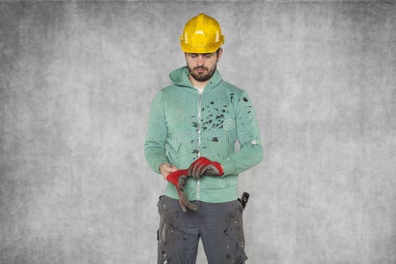 Il lavoratore indossa i guanti prima di iniziare il lavoro fotografie stock