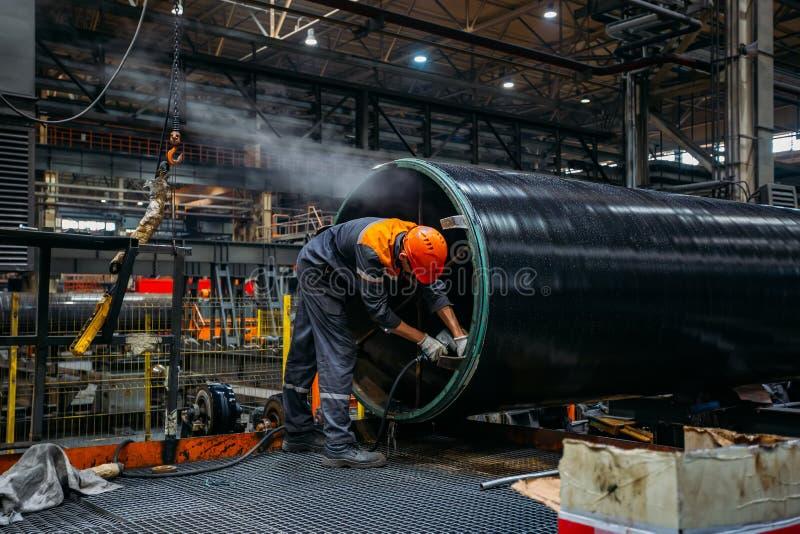 Il lavoratore installa il connettore del tubo sul tubo rivestito fotografia stock libera da diritti