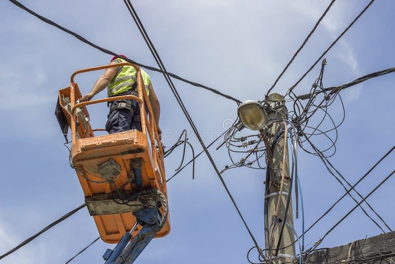 Il lavoratore installa i nuovi cavi su un palo elettrico immagini stock libere da diritti